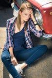 Junges attraktives Modell sitzt nahe dem Retro- Auto Stockfoto