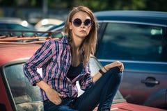 Junges attraktives Modell sitzt nahe dem Retro- Auto Lizenzfreie Stockfotografie