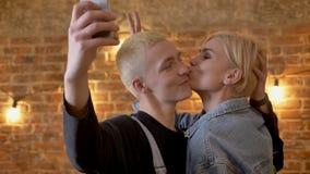 Junges attraktives Paar von Hippies macht selfie auf Smartphone und täuscht herum, Kommunikationskonzeption, Ziegelstein stock footage