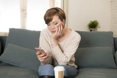 Junges attraktives rotes Frauenumkippen des Haares 30s gebohrt und schwermütig unter Verwendung Internet-APP am Handy, der zu Hau stockbilder