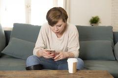 Junges attraktives rotes Frauenumkippen des Haares 30s gebohrt und schwermütig unter Verwendung Internet-APP am Handy, der zu Hau stockfotos