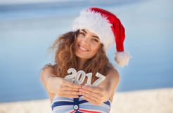 Junges, attraktives, schlankes Mädchen in einem Badeanzug und Hut von Santa Claus auf dem Strand, der Abbildung 2017 hält Lizenzfreie Stockfotografie