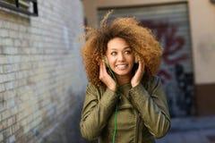 Junges attraktives schwarzes Mädchen im städtischen Hintergrund stockfotografie