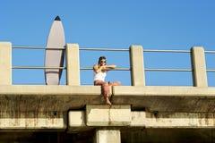 Junges attraktives Surfermädchen, das auf Pier mit Surfbrett sitzt Stockfotografie