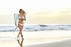 Junges attraktives Surfermädchen mit dem Brett, das aus den Wellen heraus läuft Lizenzfreie Stockbilder