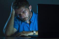 Junges attraktives und müdes unrasiertes Mannarbeiten Spät- auf Laptop-Computer im dunklen Gefühl herein frustriert und erschöpft stockfotos