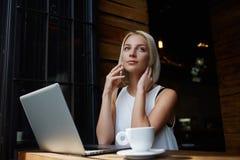 Junges attraktives weibliches Nennen mit ihrem intelligenten Telefon, beim Sitzen mit tragbarem Netzbuch in der Kaffeestube, Stockfoto