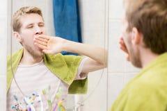 Junges bärtiges Manngegähne vor Spiegel im Badezimmer stockbilder