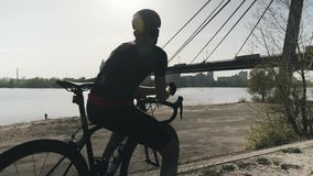 Junges b?rtiges triathlete im schwarzen Trikot und kurze Hosen, die das Blicken in Richtung des Stadtflusses, Br?cke denken und t stock video footage