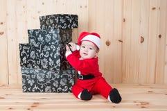 Junges Baby, das einen Weihnachtsmann-Anzug und -hut im Weihnachten in einer Scheune trägt Lizenzfreies Stockfoto