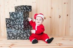 Junges Baby, das einen Weihnachtsmann-Anzug und -hut im Weihnachten in einer Scheune trägt Lizenzfreie Stockbilder