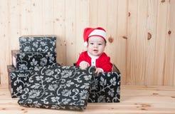 Junges Baby, das einen Weihnachtsmann-Anzug und -hut im Weihnachten in einer Scheune trägt Stockbilder