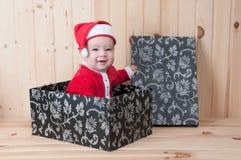 Junges Baby, das einen Weihnachtsmann-Anzug und -hut im Weihnachten in einer Scheune trägt Lizenzfreie Stockfotos