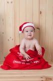 Junges Baby, das einen Weihnachtsmann-Anzug und -hut im Weihnachten in einer Scheune trägt Stockbild