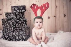 Junges Baby, das einen Weihnachtsmann-Anzug und -hut im Weihnachten in einer Scheune trägt Stockfoto