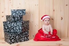 Junges Baby, das einen Weihnachtsmann-Anzug und -hut im Weihnachten in einer Scheune trägt Stockfotografie