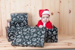 Junges Baby, das einen Weihnachtsmann-Anzug und -hut im Weihnachten in einer Scheune trägt Lizenzfreie Stockfotografie