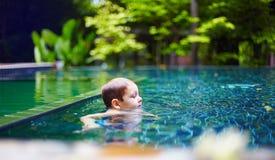 Junges Baby, das im Pool am ruhigen ruhigen Platz ralaxing ist Stockfoto