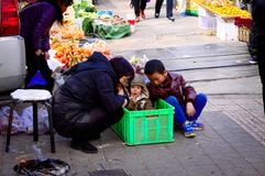 Junges Baby im Kasten mit seiner Mama und seinem Bruder - Straßenmarkt in Kunming stockbild