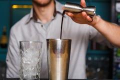 Junges Barman& x27; s, das Cocktail, auslaufenden Alkohol in Glas macht lizenzfreies stockbild