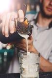 Junges Barman& x27; s, das Schusscocktail, strömenden Sirup in Glas macht lizenzfreies stockbild