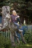 Junges Bauernmädchen, das auf großem altem Stumpf sitzt Lizenzfreie Stockbilder