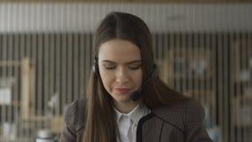 Junges Betreiberfrauenvertreter mit den Kopfhörern, die in einem Call-Center arbeiten Nach der Unterhaltung mit Kunden Frau ist m stock footage