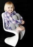 Junges blondes Baby, das auf weißem Stuhl sitzt Stockbild