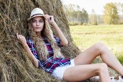 Junges blondes Bauernmädchen im Hut nahe Heuschobern Stockfoto