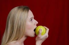 Junges blondes Beißen auf Apfel auf rotem Hintergrund Lizenzfreies Stockbild