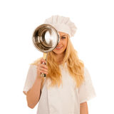 Junges blondes Chef woamn hält Küchengeschirr, während sie sich vorbereitet zu gurren Stockfoto