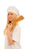 Junges blondes Chef woamn hält Küchengeschirr, während sie sich vorbereitet zu gurren Stockbild
