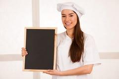 Junges blondes Chef woamn hält Küchengeschirr, während sie sich vorbereitet zu gurren Lizenzfreie Stockbilder