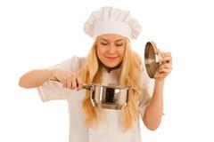 Junges blondes Chef woamn hält Küchengeschirr, während sie sich vorbereitet zu gurren Stockbilder