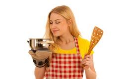 Junges blondes Frauenkochen lokalisiert über weißem Hintergrund Stockfotografie