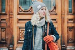 Junges blondes gelocktes Mädchen mit roten Handschuhen und Tasche, Winter lizenzfreie stockfotos
