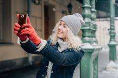 Junges blondes gelocktes touristisches Mädchen in der warmen Kleidung, die selfie macht stockbilder