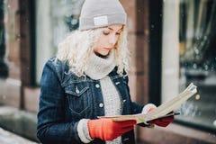 Junges blondes gelocktes touristisches Mädchen mit Karte stockfotos