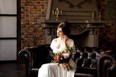 Junges blondes im Hochzeitskleid Braut in einer Luxuswohnung in einem Hochzeitskleid Lizenzfreies Stockbild