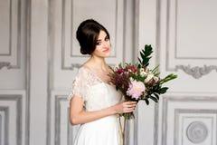 Junges blondes im Hochzeitskleid Braut in einer Luxuswohnung in einem Hochzeitskleid Stockbild