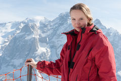 Junges blondes kaukasisches Frauenmädchen, das in den Alpenbergen mit Skiausrüstung aufwirft Stockfotografie