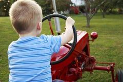 Junges blondes Kind, das vortäuscht, einen antiken roten Traktor herein zu fahren Lizenzfreies Stockbild