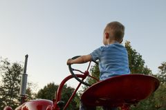 Junges blondes Kind, das vortäuscht, einen roten Traktor zu fahren Stockbild
