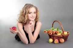Junges blondes Lügen mit Äpfeln und Blumen Stockbilder