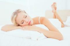 Junges blondes Lügen Schlafens auf ihrem Bett Lizenzfreie Stockfotografie