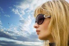 Junges blondes Mädchen auf dem Himmel Stockfotos