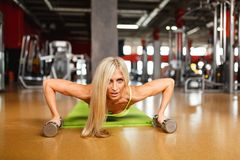 Junges blondes Mädchen bedrängt vom Boden mit Dummköpfen Innen, Fitness-Club Stockfotografie