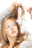 Junges blondes Mädchen betrachtet ihr Haar Stockfotografie