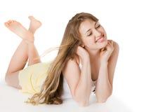 Junges blondes Mädchen, das auf dem Fußboden liegt Lizenzfreies Stockfoto