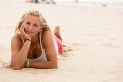 Junges blondes Mädchen, das auf dem Strand liegt in camera lächeln Stockfoto